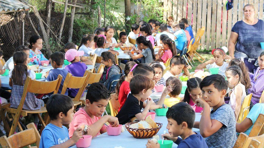 Barn spiser middag på dagsenteret.