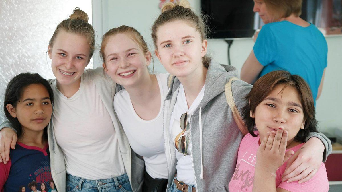 Mia Johnsen, Jenny Berntsen (tentro-leder) og Kaja Glende sammen med to av barna fra Søppelberget i Sofia.